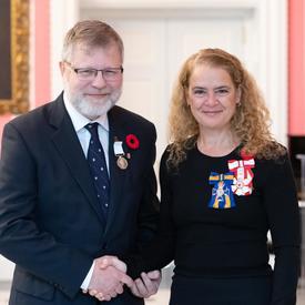 La gouverneure générale se tient à côté du récipiendaire Christopher Robert Burn qui porte la Médaille polaire qu'il vient de recevoir.