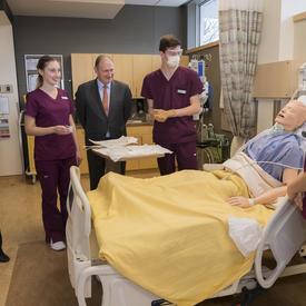 Son Excellence est debout autour d'un lit d'hôpital où des étudiants donnent des soins à un mannequin.