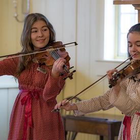 Deux femmes jouent du violon.