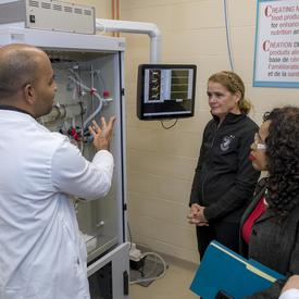 A researcher explains the digestion simulator to Her Excellency.