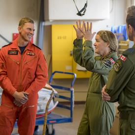 Dressed in her flight suit, the Governor General is talking to members of the 435 Squadron.