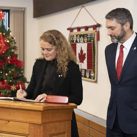 The Governor General is signing a guest book.  Sandy Silver, Premier of Yukon, stands next to her.