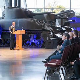 La gouverneure générale se tient devant un podium et s'adresse à la foule, dont la majorité sont en uniforme   militaire.  Un char d'assaut est derrière elle, à l'arrière-plan.