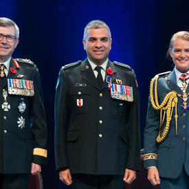 Le major Trevor Jain se tient entre le Vice-chef d'état-major de la Défense, le Lieutenant-général Paul Wynnyk (à   gauche) et Son Excellence la très honorable Julie Payette (à droite).
