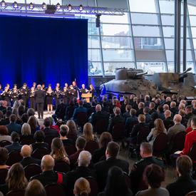 La foule assise regarde une chorale d'environ 25 jeunes, vêtus de noir, performer.