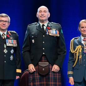 Le major James Edward Rene MacInnis se tient entre le Vice-chef d'état-major de la Défense, le Lieutenant-général   Paul Wynnyk (à gauche) et Son Excellence la très honorable Julie Payette (à droite)