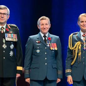 Le major Jennifer Lynn Morrison se tient entre le Vice-chef d'état-major de la Défense, le Lieutenant-général Paul   Wynnyk (à gauche) et Son Excellence la très honorable Julie Payette (à droite).