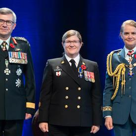 Le premier maître de 2e classe Marie Nathalie Isabelle Scalabrini se tient entre le Vice-chef d'état-major de la   Défense, le Lieutenant-général Paul Wynnyk (à gauche) et Son Excellence la très honorable Julie Payette (à   droite).
