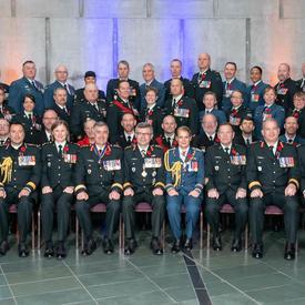 Une photo de groupe des 69 membres nouvellement investis de l'Ordre du mérite militaire. Le Vice-chef d'état-major   de la Défense, le Lieutenant-général Paul Wynnyk, et Son Excellence la très honorable Julie Payette sont assis au   centre du premier rang