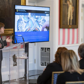 Seen from the side, a woman speaks at a podium while a group of people is sitting on chairs in front of her. A website is shown on a large TV screen beside her.