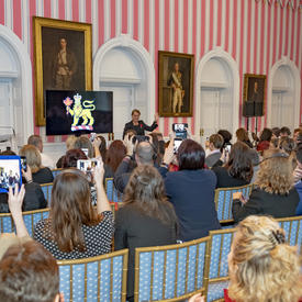 Governor General of Canada Julie Payette, standing, addresses a group of people, sitting. Many take photos on their smart devices. A large TV screen behind her shows the vice-regal lion symbol.