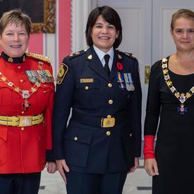 La gouverneure générale et le commissaire de la GRC prennent une photo avec un récipiendaire de l'Ordre du mérite des corps policiers.