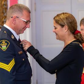 La gouverneure générale épingle une médaille sur la poitrine d'un récipiendaire de l'Ordre du mérite des corps policiers.