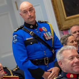 Un récipiendaire de l'Ordre du mérite des corps policiers se tient debout avant de s'approcher de l'avant de la salle pour accepter sa médaille.