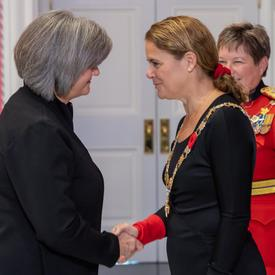 La gouverneure générale serre la main d'un récipiendaire de l'Ordre du mérite des corps policiers.