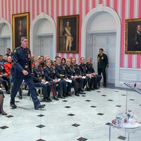 Un récipiendaire de l'Ordre du mérite des corps policiers se dirige vers l'avant de la salle de tente pour recevoir sa médaille.