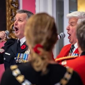 L'hymne national est chanté par deux chanteurs alors que le public se tient debout en solidarité.