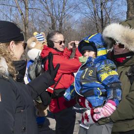 Son Excellence se tient debout devant la caméra et fait signe à un enfant tenu dans les bras de sa mère.  Ils sont debout à l'extérieur en tenue d'hiver. Derrière eux, il y a une foule de gens.