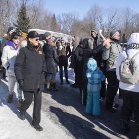 La gouverneure générale se promène à l'extérieur dans son manteau d'hiver.  Elle est entourée d'une foule de gens.