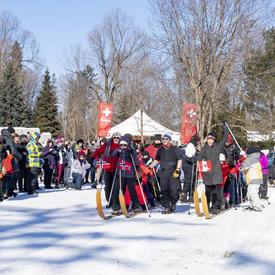 Il y a une grande foule qui se tient à l'extérieur en hiver.  Au centre de la photo se trouvent deux rangées de personnes attachées à de grands skis de fond multi-personnes.  Ils sont à la ligne de départ et se préparent à être une course amicale.