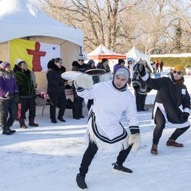 Un groupe de jeunes joue du tambour et exécute une danse traditionnelle inuite. Le drapeau du Nunavut est arboré derrière eux.