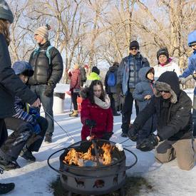 Les gens s'assoient autour d'un feu, rôtissant des guimauves.