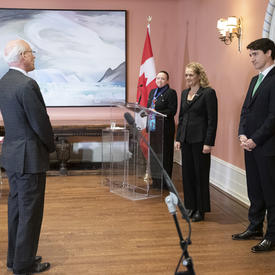 Michael Wernick, clerk of the Privy Council, stands in front of Governor General Julie Payette and Prime Minister Justin Trudeau.   In the corner of the room stands the MC behind a podium.