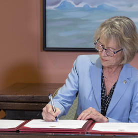 Minister Murray signs the oath book.