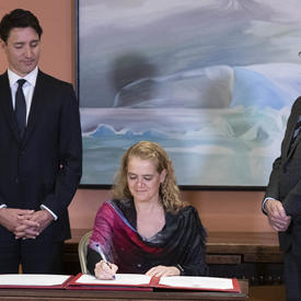 The Governor General signs the oath book. The Prime Minister and the Clerk of the Privy Councillor are on each side of her.