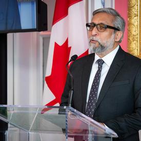 Ali Kazimi prononce un discours à partir d'un podium.