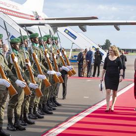 La gouverneure générale marche sur le tapis rouge.