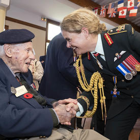 La gouverneure générale serre la main d'un ancien combattant.