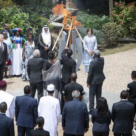 Un groupe de personnes allume la flamme du Souvenir avec une torche.