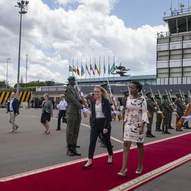 La gouverneure générale marche sur un tapis rouge en direction vers l'avion.
