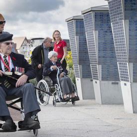 Deux personnes âgées en fauteuil roulant, poussées chacune par une autre personne, passent devant un monument.