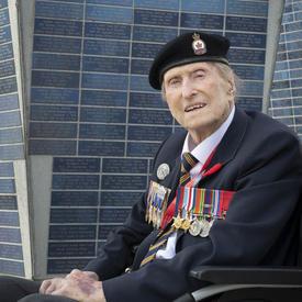 Un ancien combattant, portant plusieurs médailles, est assis dans un fauteuil roulant, regardant directement l'appareil photo. un grand monument se trouve derrière lui.