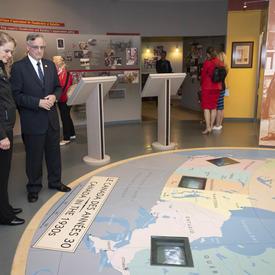 La gouverneure générale Julie Payette se tient debout dans une pièce en regardant une carte sur le plancher devant elle. Un homme debout à sa gauche lui donne des explications sur ce qu'elle voit.
