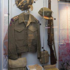 Des éléments de l'uniforme d'un soldat canadien de la Seconde Guerre mondiale sont exposés dans une valise sur un mur.