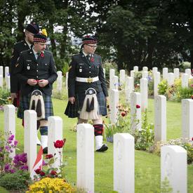 Trois hommes en uniforme marchent entre deux rangées de pierres tombales au cimetière de guerre canadien de Bény-sur-Mer.
