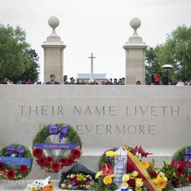 Des fleurs sont déposées devant un monument au Cimetière de guerre canadien de Bény-sur-Mer.