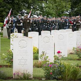Des rangées de pierres tombales blanches au cimetière de guerre canadien de Bény-sur-Mer pour commémorer le 75e anniversaire du jour J. Les militaires sont alignés à distance.