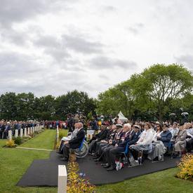 Une foule est assise lors d'une cérémonie au Cimetière de guerre canadien de Bény-sur-Mer.