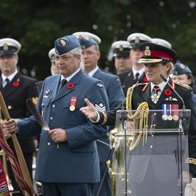 La gouverneure générale Julie Payette, en uniforme de la Force aérienne du Canada, prononce une allocution à une tribune. Elle est entourée de militaires.