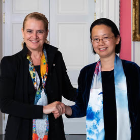Lin Cai serre la main de la gouverneure générale.