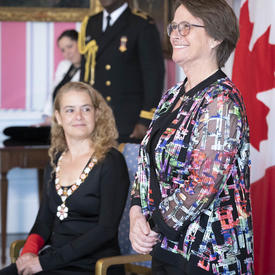 Claudine Roy stands at the front of the room alongside the Governor General
