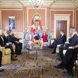 La présidente de la République de Croatie et la gouverneure générale sont assises sur des chaises et elles se  parlent.
