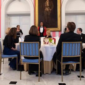 Photo de la table d'honneur et de la gouverneure générale qui prononce une allocution à l'occasion d'un dîner d'État.