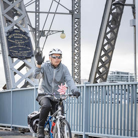 A cyclist on Alexandria Bridge waves