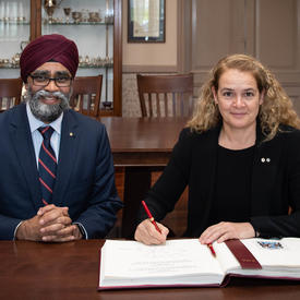 The Governor General and the Honourable Harjit S. Sajjan, Minister of National Defence sign the Royal Military College of Canada's guest book.