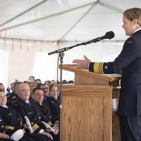 La gouverneure générale Julie Payette est vue de profil gauche, s'adressant à une tribune, devant un auditoire assis, sous une tente blanche.